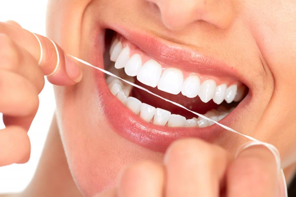 Person with white teeth flossing